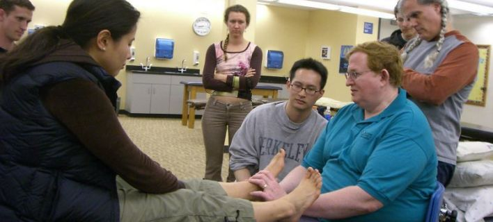 Medical Students and physician review a technique of osteopathic manipulative medicine at Touro University College of osteopathic medicine. © Foto: OsteopathicFreak (Own work) [Public domain], via Wikimedia Commons